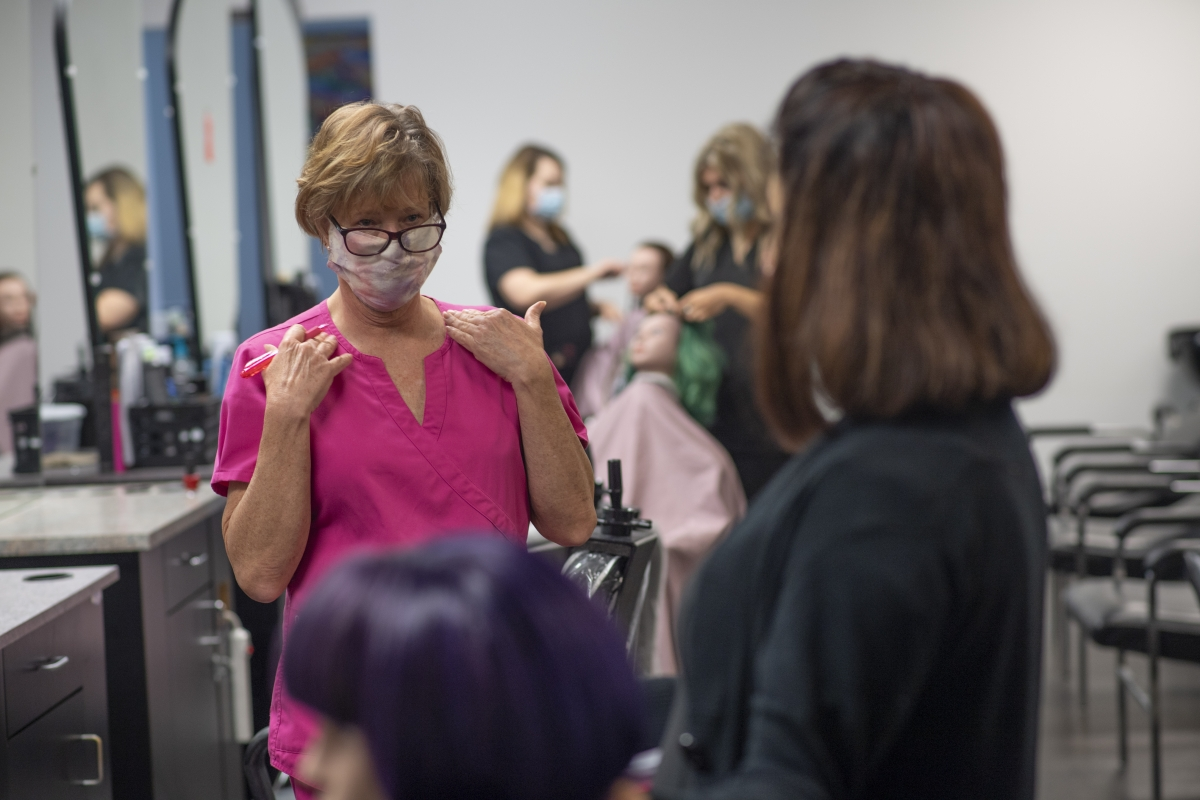 A female instructor speaks to a young female cosmetology student who is practicing on a mannequins hair