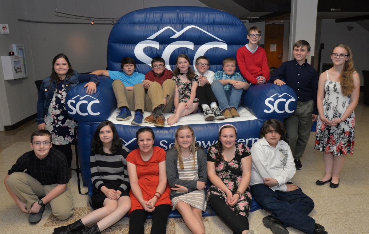 More than a dozen students pose on a blue inflatable chair with white SCC logos.