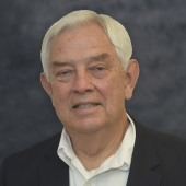 Man in white shirt and suit coat stands in front of gray background.