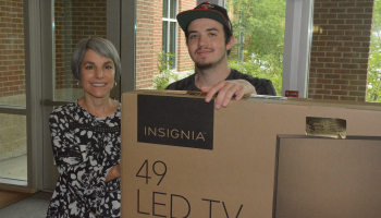 Man and woman hold a cardboard box that contains a flat-screen TV.