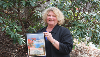 Kay Wolf pictured with the award she and the English Learners Team received.
