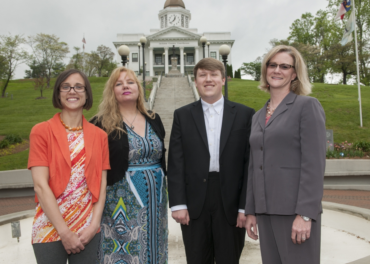 Three students, dressed professionally, stand beside their professor in front of the historic Jackson County Courthouse in Sylva, N.C.